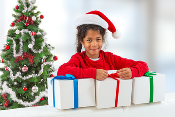 Merry Christmas and happy holidays. New Year 2020. Portrait of smiling cute little girl with Santa Claus hat holding gift box.