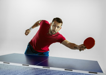 Wall Mural - Traffic. Young man plays table tennis on white studio background. Model plays ping pong. Concept of leisure activity, sport, human emotions in gameplay, healthy lifestyle, motion, action, movement.