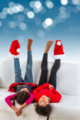 little girl lying on the sofa on the sofa are having fun with Santa Claus hat on their feet over a blue bokeh