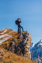 Teenager and adult at the peak of a mountain in the Alps