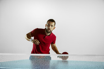 Wall Mural - Rush. Young man plays table tennis on white studio background. Model plays ping pong. Concept of leisure activity, sport, human emotions in gameplay, healthy lifestyle, motion, action, movement.