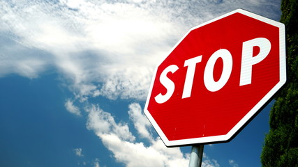 Octagonal STOP sign on a red background with blue sky with clouds. conceptual photo