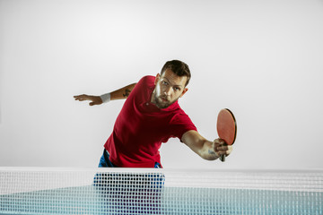 Wall Mural - Emotions. Young man plays table tennis on white studio background. Model plays ping pong. Concept of leisure activity, sport, human emotions in gameplay, healthy lifestyle, motion, action, movement.