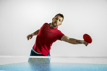 Wall Mural - Joy. Young man plays table tennis on white studio background. Model plays ping pong. Concept of leisure activity, sport, human emotions in gameplay, healthy lifestyle, motion, action, movement.