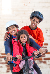 6 and 12 years old girl and boys riding a bicycle. in the garden