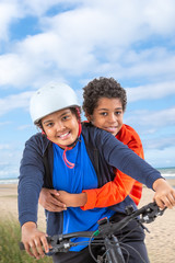 10 and 112 years old boys riding a bicycle. over a beach background