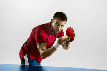Wall Mural - Flexible. Young man plays table tennis on white studio background. Model plays ping pong. Concept of leisure activity, sport, human emotions in gameplay, healthy lifestyle, motion, action, movement.