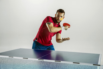 Wall Mural - Fight. Young man plays table tennis on white studio background. Model plays ping pong. Concept of leisure activity, sport, human emotions in gameplay, healthy lifestyle, motion, action, movement.