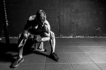 Young strong muscular sweaty fit man biceps muscle workout cross training with heavy dumbbell in the gym dark image with shadows real people black and white Wall mural
