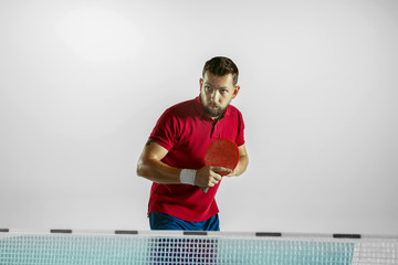 Wall Mural - Experiences. Young man plays table tennis on white studio background. Model plays ping pong. Concept of leisure activity, sport, human emotions in gameplay, healthy lifestyle, motion, action, movement