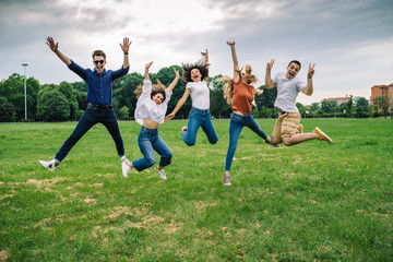 Papiers peints Attraction parc Group of five friends jump into the air with their hands up - Millennials have fun together at the park in the summer