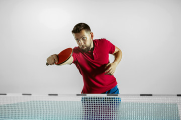 Wall Mural - Run. Young man plays table tennis on white studio background. Model plays ping pong. Concept of leisure activity, sport, human emotions in gameplay, healthy lifestyle, motion, action, movement.