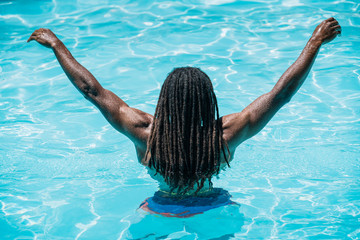 Black boy with dreadlocks on his back in a pool with arms raised