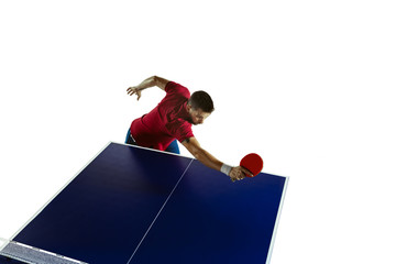 Wall Mural - Wait. Young man plays table tennis on white studio background. Model plays ping pong. Concept of leisure activity, sport, human emotions in gameplay, healthy lifestyle, motion, action, movement.