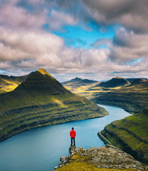 Photo sur Aluminium Bleu ciel Hiker enjoys views over fjords from a mountain near Funningur on Faroe Islands