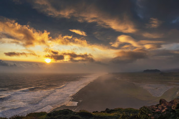 Wall Mural - Dramatic sunset above a black beach viewed from Dyrholaey viewpoint in Iceland
