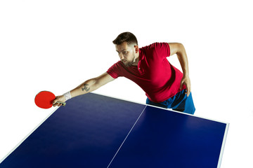 Wall Mural - Intense. Young man plays table tennis on white studio background. Model plays ping pong. Concept of leisure activity, sport, human emotions in gameplay, healthy lifestyle, motion, action, movement.