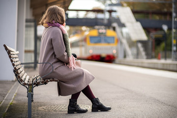 Young woman sitting on the bench waiting for the train. Autumn season