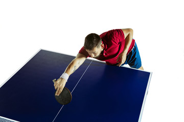 Wall Mural - Keen. Young man plays table tennis on white studio background. Model plays ping pong. Concept of leisure activity, sport, human emotions in gameplay, healthy lifestyle, motion, action, movement.