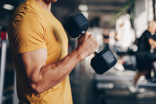 authentic image, detail close up of fit coach man lifting weight, training bicep curl in the gym. concept of weight loss and healthy living.
