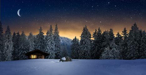 Gemütliche Holzhütte mit Beleuchtetem Fenster in Wnterwald bei Nacht im Winter