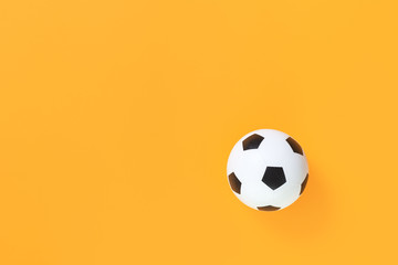 Soccer ball against trendy yellow background