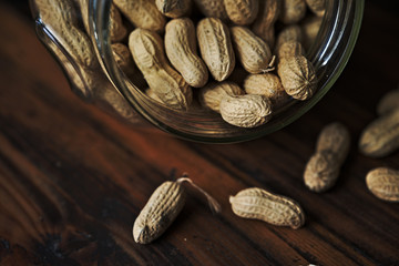 Close up of peanuts in a jar on rustic wooden background
