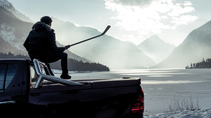 Man sitting on the hood of a car. Hockey player looking for frozen pond. Shiny red pickup truck on ice covered road and snowy rural landscape. Offroad 4x4