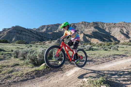 A young boy riding his mountain bike on the trails in Fruita, Colorado