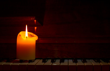 burning candle on piano key