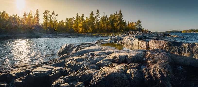 Beautiful panorama of a rocky shore. Nordic sunrise or sunset.  Close-up of  big stones
