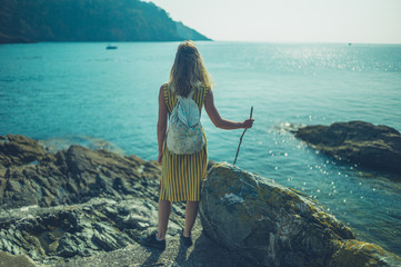 Young woman with stick standing by the sea