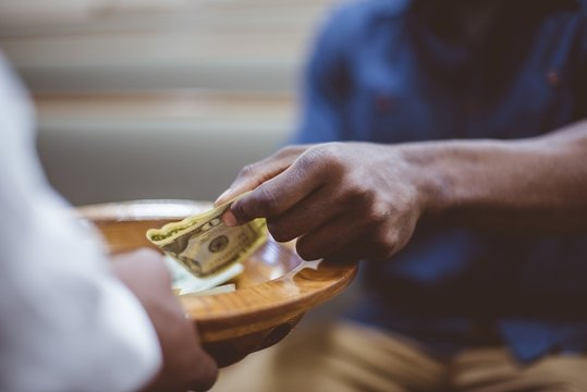 Closeup shot of a male donating money for church with a blurred background