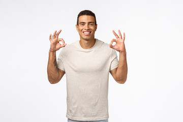 Optimistic, satisfied good-looking man with tattoo, showing okay, ok or good sign, smiling in approval, nod agreement, give positive reply, recommend product, think smth perfect, white background