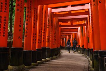 A couple under red Torii Gate at Fushimi Inari Taisha, Fushimi-ku, Kyoto, Japan