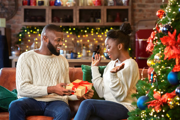 Happy black guy giving present to wife, congratulating with Christmas