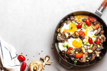 Tasty and hearty breakfast or snack. Fried eggs with mushrooms, tomatoes and onions in a pan on a grey background, top view, free space for text.