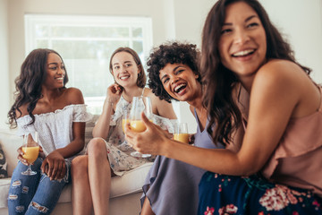 Diverse group of female friends enjoying at a party and laughing. Women friends having a party at home and looking away.