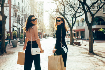 Two female friends having fun on a shopping spree in the city. Women with shopping bags walking on city street.
