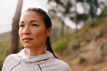 Close up portrait of healthy young woman standing outdoors and looking away. Confident female runner in morning.