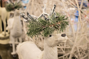 Close-up cropped white sparkly reindeer Christmas decoration with garland of snow covered greenery around horns - selective focus against blurred background