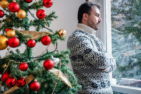 Sad man portrait feeling negative emotions during christmas celebrations