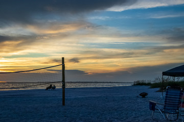 Couple sits on the beach together while watching the sunset, amomgst volleyball net, beach chairs and firepit