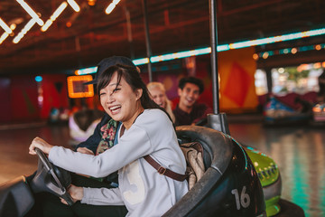 Foto op Aluminium Amusementspark Happy young girl driving a bumper car with friends in background at amusement park