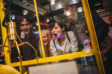Excited young friends playing toy grabbing game at amusement park. Happy woman selecting a random soft toy in a vending machine.