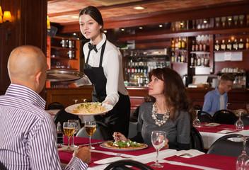 Fotobehang Restaurant Young waitress serving couple