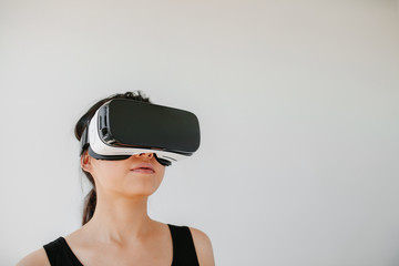Shot of young woman using the virtual reality headset against grey background. Asian female model wearing VR goggles.