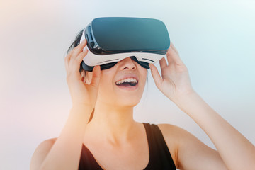 Close up shot of smiling young woman using the VR goggles against grey background with sunflare effect. Asian female model wearing virtual reality headset.