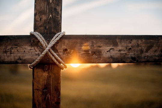 Closeup shot of a wooden cross with the sun in the blurred background