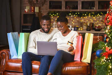 Afro couple buying gifts online, using laptop and credit card
